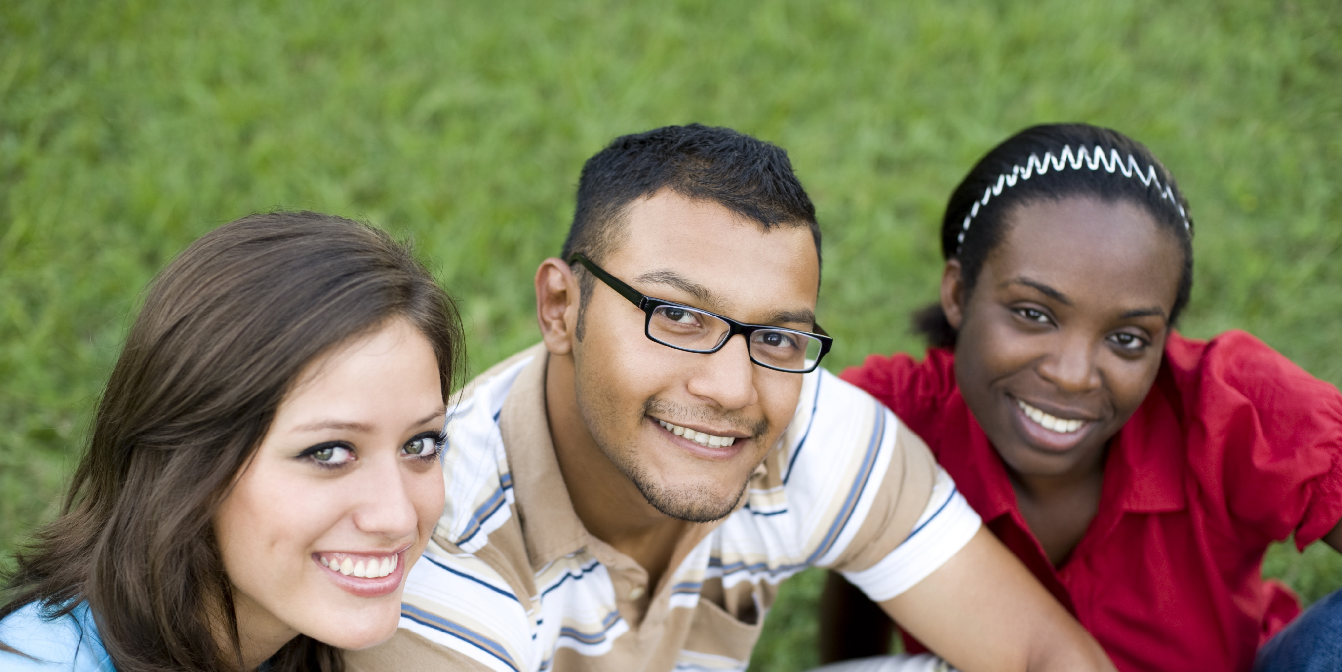 A white woman, a latino man, and a black woman sit together and look up to the camera smiling.